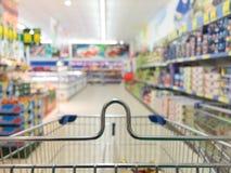 Visión desde la carretilla del carro de la compra en la tienda del supermercado. Venta al por menor. Imagen de archivo libre de regalías