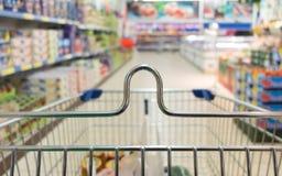 Visión desde la carretilla del carro de la compra en la tienda del supermercado. Venta al por menor. Foto de archivo libre de regalías