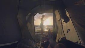 Visión desde la chica joven turística de la silueta de la tienda en paisaje de oro de la puesta del sol en el mar y los pies masc metrajes