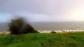Visión desde la colina en un día lluvioso en las ondas, vegetación verde, lluvia, kitesurfing almacen de video