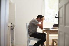 Visión desde la entrada del adolescente infeliz que estudia en cocina Foto de archivo libre de regalías