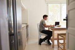 Visión desde la entrada del adolescente que estudia en una cocina Imagenes de archivo