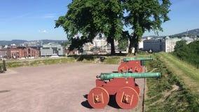 Visión desde la fortaleza de Akershus en ayuntamiento Oslo y cañones históricos almacen de metraje de vídeo