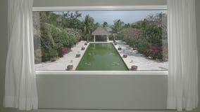 Visión desde la habitación de calmar el centro turístico tropical con el jardín y la piscina Placa del fondo, fondo video dominan metrajes