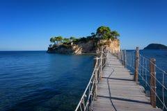 Visión desde la isla de Agios Sostis y del camafeo Una pequeña isla hermosa con el puente de madera y la turquesa riegan Zakyntho Imagen de archivo libre de regalías