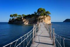 Visión desde la isla de Agios Sostis y del camafeo Una pequeña isla hermosa con el puente de madera y la turquesa riegan Zakyntho Imagenes de archivo