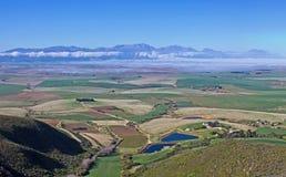 Visión desde la montaña a través de tierras de labrantío verdes Fotos de archivo libres de regalías