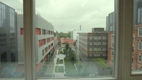 Visión desde la oficina moderna a los edificios en yarda encendido al aire libre almacen de video