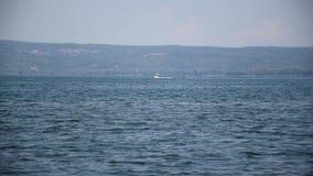 Visión desde la orilla del lago del barco en la navegación almacen de metraje de vídeo