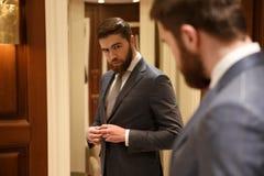 Visión desde la parte posterior del hombre hermoso que mira el espejo imagen de archivo