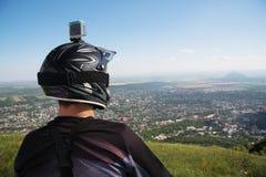 Visión desde la parte posterior El jinete de MTB mira de la montaña a la ciudad que está en alguna parte abajo allí Foto de archivo libre de regalías