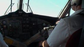 Visión desde la parte posterior en dos pilotos en la carlinga plana en el fondo de la ventana almacen de video