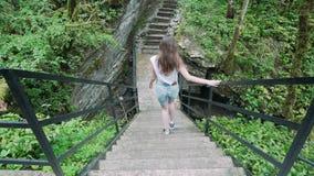 Visión desde la parte posterior: la muchacha desciende las escaleras en la selva tropical almacen de metraje de vídeo