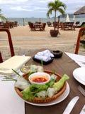 Visión desde la tabla con una placa de rollos vietnamitas en un paisaje marino tropical imágenes de archivo libres de regalías