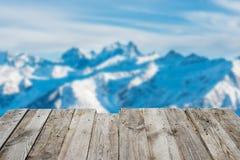 Visión desde la tabla de madera vacía a las montañas del invierno imagenes de archivo