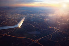 Visión desde la ventana del aeroplano del aterrizaje de la ciudad en la puesta del sol fotografía de archivo libre de regalías