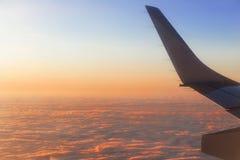 Visión desde la ventana del aeroplano en el amanecer durante el vuelo Fotografía de archivo libre de regalías