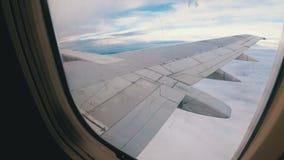 Visión desde la ventana en el ala de un vuelo de los aviones de pasajero bajo sobre las nubes almacen de video