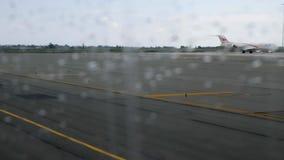 Visión desde la ventana plana con gotas de lluvia en pista del aeropuerto mientras que mudanza del avión metrajes