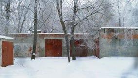 Visión desde la ventana sobre el edificio agrícola del ladrillo Está nevando afuera Invierno metrajes
