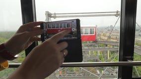 Visión desde las cabinas de la ventana de la noria Visto el cielo nublado, los árboles y los edificios, Viena, Austria almacen de metraje de vídeo