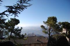 Visi?n desde San Marino al Apennines circundante Casas medievales rodeadas por los pinos imagenes de archivo