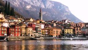 Visión desde un barco de las orillas del lago Como con la ciudad de Varenna y de las montañas italianas en el fondo, vídeo de la  almacen de metraje de vídeo