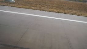Visión desde un jet que se desliza en pista del aeropuerto según lo visto por dentro de los aviones El avión saca en un aeropuert almacen de metraje de vídeo