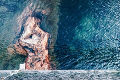 Visión desde un puente derecho abajo en el agua azul y en una roca Foto de archivo libre de regalías