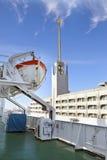 Visión desde un tablero del buque en el edificio de Marine Station (puerto marítimo) en puerto y un bote salvavidas en el primero Imagen de archivo