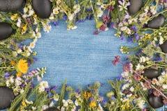 Visión directa, fondo del dril de algodón en el centro, flores salvajes en el contorno de la superficie de la mezclilla Copie el  imagenes de archivo