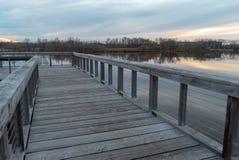 Visión dramática desde un muelle de madera del lago que pasa por alto la calma en un lago y un bosque en la puesta del sol en oto imágenes de archivo libres de regalías