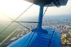 Visión en el aeroplano de la porta de un biplano de los aviones del turbopropulsor en las calles y las casas de la ciudad Fotos de archivo libres de regalías