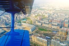 Visión en el aeroplano de la porta de un biplano de los aviones del turbopropulsor en las calles y las casas de la ciudad Imagen de archivo libre de regalías