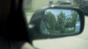 Visión en el espejo de la vista posterior en el coche almacen de metraje de vídeo
