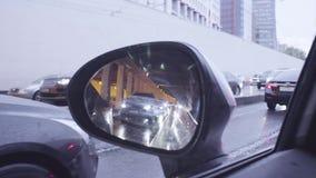 Visión en espejo retrovisor del ` s del coche en la calle de la ciudad almacen de metraje de vídeo
