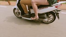 Visión en los pies de la muchacha y del muchacho en la conducción de la vespa Día asoleado del verano traveling Viaje ruedas almacen de metraje de vídeo