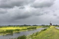Visión escénica con agua, la hierba, las nubes tormentosas y el ambiente del ithe del molino de viento de Zwammerdam Los Países B foto de archivo libre de regalías