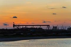 Visión escénica sobre las grúas y el puerto del envase de Pointe-Noire durante puesta del sol roja Foto de archivo libre de regalías