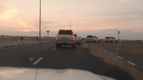 Visión fuera del coche en los jeeps que conducen a lo largo del camino en la puesta del sol del desierto almacen de video
