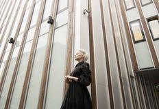 Visión granangular, mujer en vestido negro largo con el corte de pelo blanco corto, construyendo Imagenes de archivo