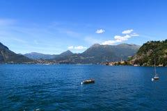 Visión hacia el lago Como con los barcos y el pueblo Varenna con las montañas en Lombardía Imagen de archivo libre de regalías