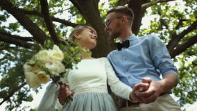 Visión inferior Beso hermoso joven de los recienes casados contra un fondo del árbol verde en el parque almacen de metraje de vídeo