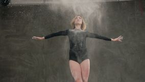 Visión inferior El baile rubio de la muchacha delgada en el bailarín blanco de la nube A del polvo se vistió en cuerpo negro que  metrajes