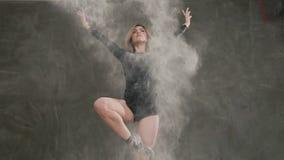Visión inferior Un bailarín se vistió en cuerpo negro que el traje realiza una danza moderna en una nube del polvo o del humo bla almacen de video