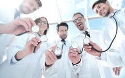 Visión inferior un grupo de doctores ha puesto sus estetoscopios juntos imagen de archivo