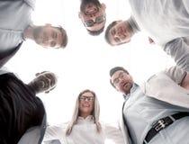 Visión inferior un grupo de gente joven se une, formando un círculo fotos de archivo libres de regalías
