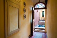 Visión interior desde el vestíbulo a través de la puerta abierta al patio del foto de archivo