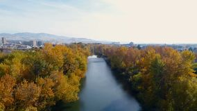 Visión a lo largo de Boise River con los árboles de la caída del puente y de Boise Skyline almacen de video