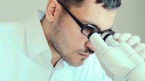 Visión masculina joven del doctor a través del microscopio almacen de metraje de vídeo